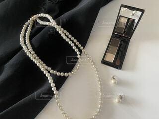 無造作に置いたドレスとアイブローパウダーとパールのアクセサリーの写真・画像素材[4349737]