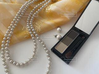 無造作に置いたドレスとアイブローパウダーとパールのアクセサリーの写真・画像素材[4349747]
