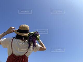 青空と花束を持った女性の写真・画像素材[4561576]