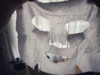部屋の中でシートマスクを持っている女性の写真・画像素材[4567126]