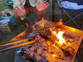 キャンプサイトで焚き火を囲んでる人の写真・画像素材[4596311]