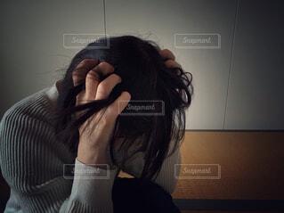 暗い部屋で頭を抱えてうずくまる人の写真・画像素材[4620822]