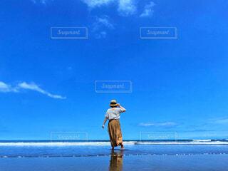 浜辺を裸足でたたずむ女性の写真・画像素材[4628911]