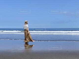 裸足で砂浜を歩いている女性の写真・画像素材[4628946]
