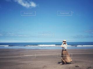裸足で砂浜を歩いている女性の写真・画像素材[4628955]