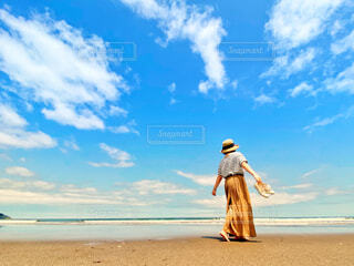 裸足で波打ち際を歩く女性の写真・画像素材[4628967]