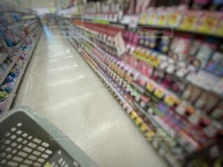 ドラッグストアのヘアケア商品が並ぶ棚と買い物かごの写真・画像素材[4772079]