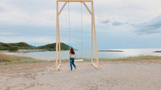 水の体の横にある砂浜に立っている人の写真・画像素材[1478471]
