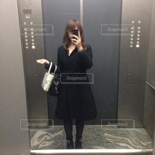 カメラにポーズ鏡の前に立っている人の写真・画像素材[1482303]