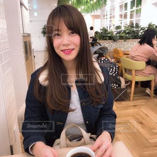 テーブルの上に座っている女性の写真・画像素材[1803010]