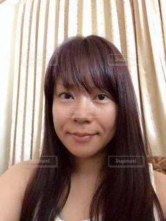カーテンの前で微笑む女性のクローズアップの写真・画像素材[2374688]