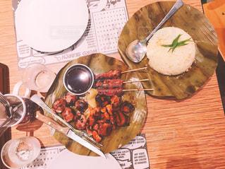 食品のプレートをのせた木製テーブルの写真・画像素材[1691720]