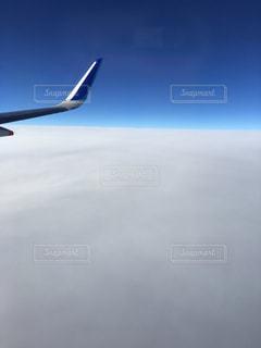 曇りの青い空を飛んでいるジェット旅客機の写真・画像素材[1561977]