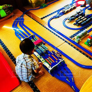 おもちゃのプラレールと電車を眺めている男の子の後ろ姿の写真・画像素材[1483033]