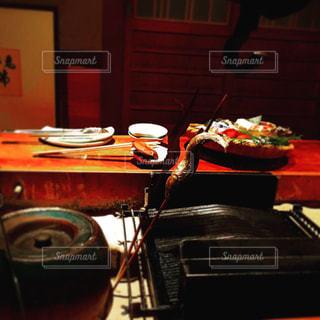 テーブルに囲まれた囲炉裏端で串打ちされた魚の丸焼きが二匹刺さっている食事風景と、カゴに盛り付けられた食材の写真・画像素材[1484298]