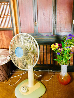 古民家カフェの席から見える閉じたお仏壇を背にした古びた扇風機と花びんが置かれた味のある風景の写真・画像素材[1502110]