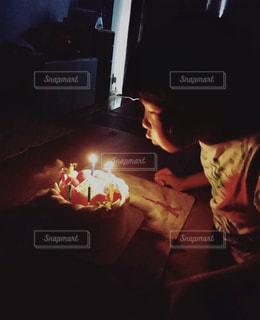 誕生日ケーキのキャンドルを吹き消す女の子の写真・画像素材[1494189]