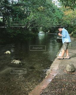 川辺でジュースを飲む男性の横顔の写真・画像素材[1512877]