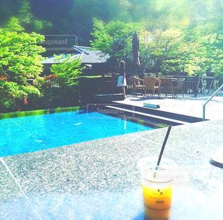 緑がキレイでプールが見えるカフェでドリンクを飲みながらのんびり🍹の写真・画像素材[1563426]