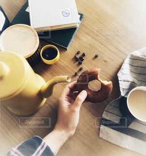 木製のテーブルの上のひと口かじったドーナツとコーヒー☕️🍩の写真・画像素材[1566438]