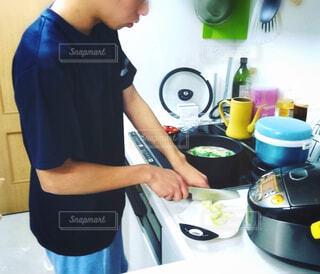 キッチンで料理する20代の男性の写真・画像素材[1567235]