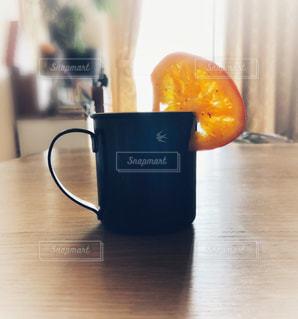 木製テーブルの上にドライフルーツのオレンジが掛かっている琺瑯のマグカップの写真・画像素材[1595096]