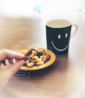 テーブルの上のコーヒー カップとナッツ🥜☕️の写真・画像素材[1630857]
