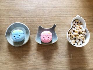 木製テーブルの上に豆まき用の豆と鬼の生菓子の写真・画像素材[1750455]