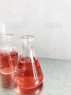 ガラス製の三角フラスコと集気ビンにピンクの液体の写真・画像素材[1810330]