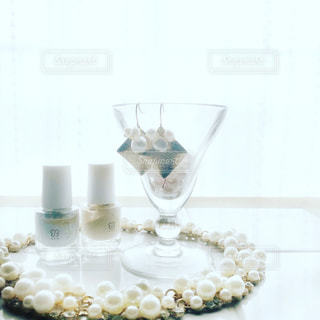 明るい窓辺のタイルテーブルの上にパールのネックレスとピアスとネイルの写真・画像素材[1813830]