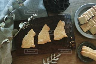 木目のテーブルの上に3匹の猫のクッキーとインテリアグリーンの置き画の写真・画像素材[1843992]