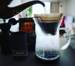 キッチンカウンターにてハンドドリップでコーヒーを淹れているところの写真・画像素材[1846220]
