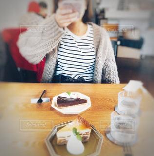 カフェ店内にてケーキをスマホで撮影する女の子の写真・画像素材[1852200]