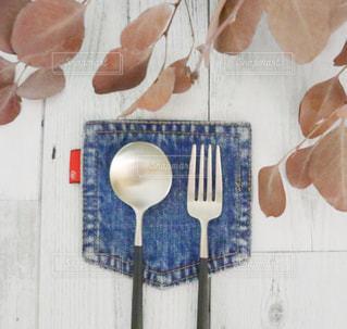 キッチンのテーブルの上のデニムのコースターの上のスプーンとフォークの写真・画像素材[2055435]