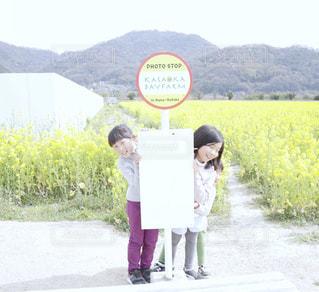 岡山県笠岡市の笠岡ベイファームの菜の花畑でバス停の前に立っている2人の子供の写真・画像素材[2096116]
