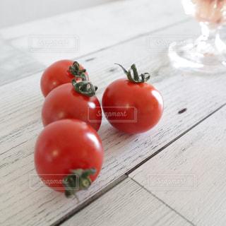 木製のテーブルの上に座っている赤いりんごの写真・画像素材[2099094]
