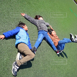 芝生に寝転がっている3人の子供たちの写真・画像素材[2103905]