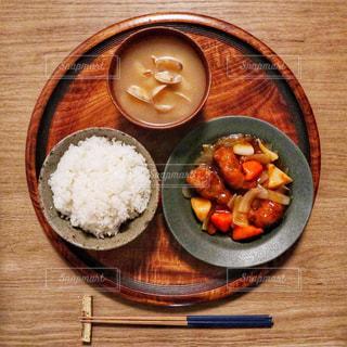 テーブルの上にお盆に乗った酢豚とあさりの味噌汁とごはんの写真・画像素材[2106465]