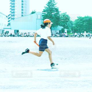 運動会のリレーでバトンを持ち走る女の子の写真・画像素材[2170389]