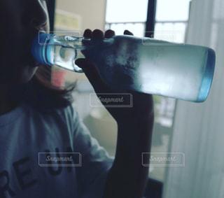 窓辺でラムネを飲んでいる女の子の写真・画像素材[2177272]