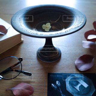 木目のテーブルの上に花器とめがねとユーカリの写真・画像素材[2227610]