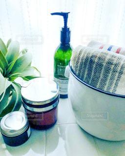 洗面周りのホーローに入ったタオルとハンドソープのボトルとヘアワックス瓶の写真・画像素材[2246746]
