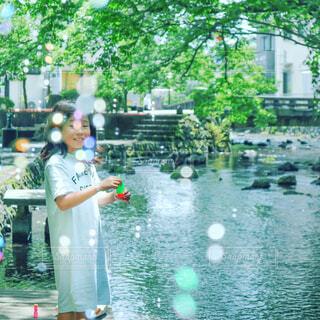 静岡県三島市の源兵衛川にてシャボン玉を吹く女の子の写真・画像素材[2248881]