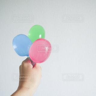 プラスチックの容器に入った3色のゼリーを持つ手の写真・画像素材[2260653]