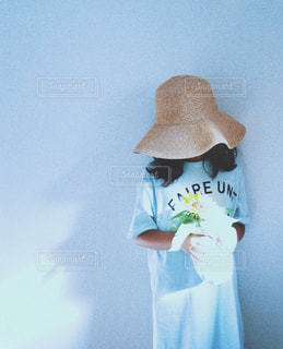 一輪のひまわりを持つ麦わら帽子をかぶった女の子の写真・画像素材[2325658]