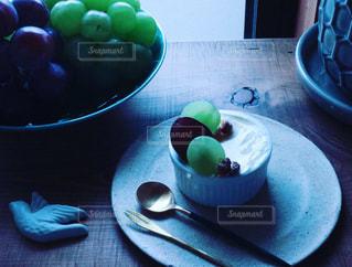 テーブルの上に座っている果物のボウルとケーキの写真・画像素材[2448479]