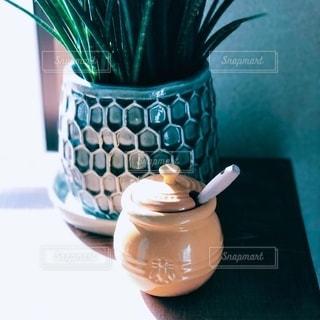 テーブルの上に座っている花でいっぱいの花瓶の写真・画像素材[2546366]