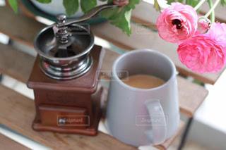 一杯のコーヒーとテーブルの上の花の写真・画像素材[1508542]