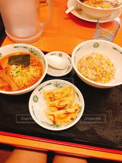 テーブルの上の皿の上に食べ物のボウルの写真・画像素材[1101558]