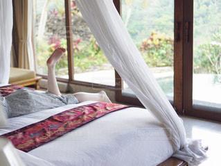 ウィンドウの横に座っている大きな白いベッドの写真・画像素材[1708465]